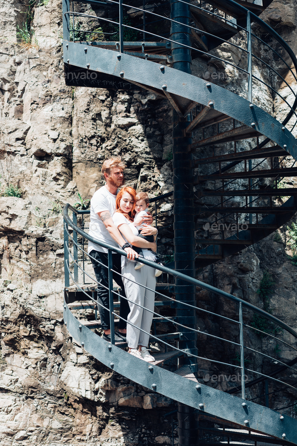 The family standing on a spiral staircase - Stock Photo - Images