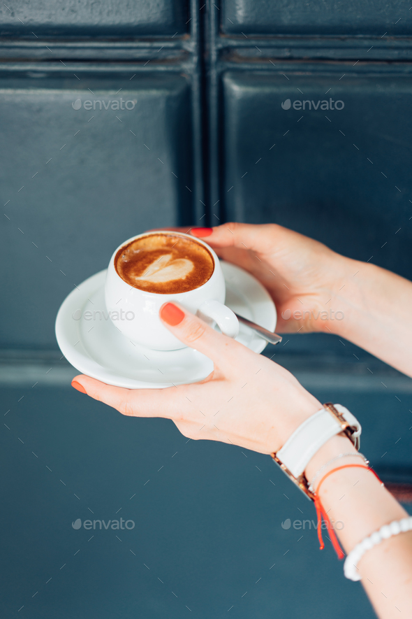 woman holding hot cup of coffee - Stock Photo - Images