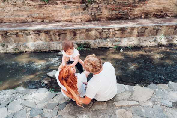 The family sit on the river bank - Stock Photo - Images