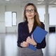 Attractive Woman with Papers in Office. Young Woman Holding Tablet with Papers in Empty Office Space