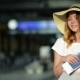 Amazing Young Girl Wearing Summer Hat Is Holding Passport and Ticket at the Airport. Travelling