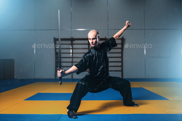 Wushu fighter with sword in action, martial arts - Stock Photo - Images