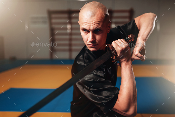 Wushu master with blade in action, martial arts - Stock Photo - Images