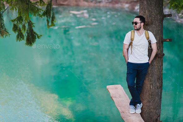 Bearded man model poses alongside a Green water Lake. - Stock Photo - Images