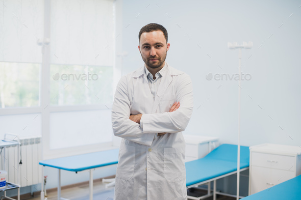 Portrait of a serious confident male doctor standing with arms crossed at medical office - Stock Photo - Images