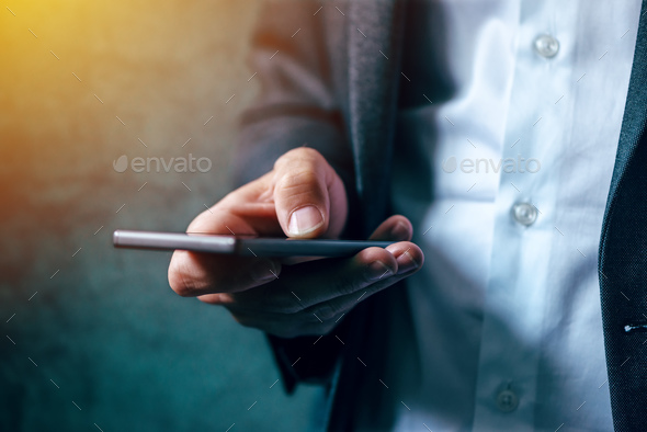 Hand with mobile phone texting - Stock Photo - Images