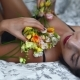 Sensual Woman Posing on Bed with Flowers
