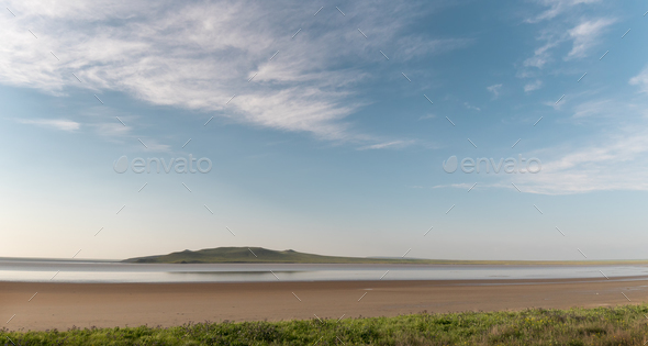 Lake and hills under a blue sky with clouds - Stock Photo - Images
