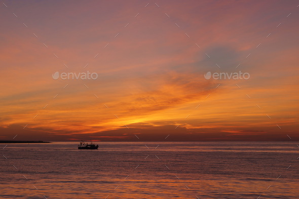 Small fishing boat in the sea at sunset - Stock Photo - Images