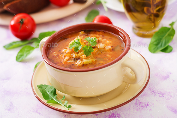 Soup with pickled cucumbers and pearl barley - rassolnik on a light background. - Stock Photo - Images