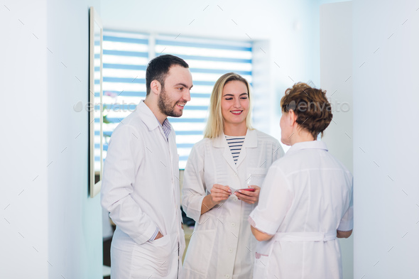 Mature doctor discussing with nurses in a hallway hospital. Doctor discussing patient case status - Stock Photo - Images
