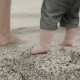 Baby First Steps on the Sand Whit Parents.  of Feet