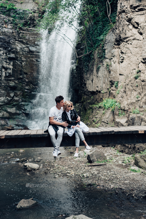 A guy and girl are sitting on a bridge - Stock Photo - Images