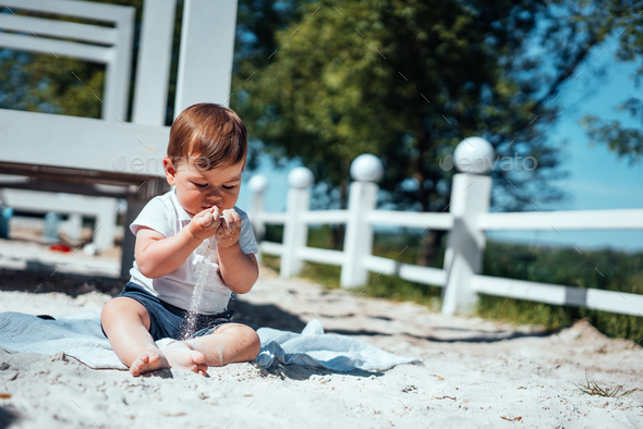 Little baby boy sitting on the sand - Stock Photo - Images