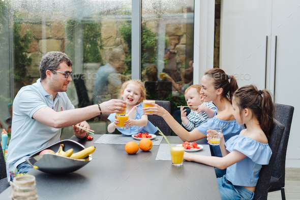 Happy family eating fresh fruit breakfast - Stock Photo - Images