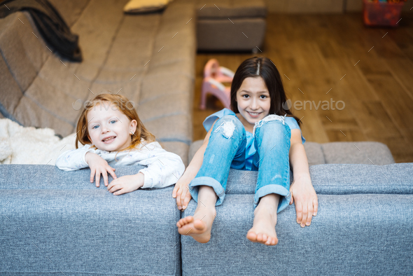 Elder and younger daughter on the big couch - Stock Photo - Images