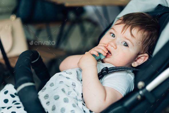 Little boy sitting in a baby carriage - Stock Photo - Images