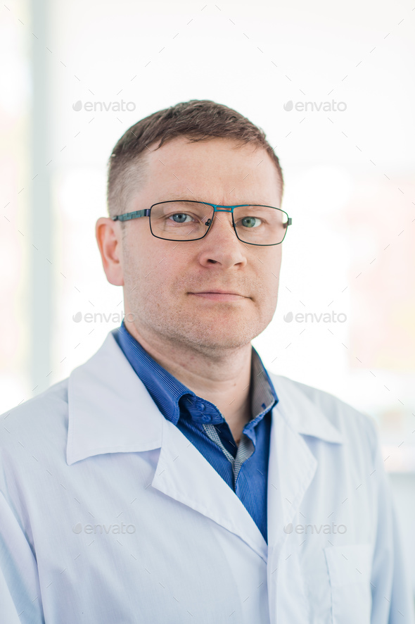 Portrait of confident mature male surgeon standing arms crossed in hospital - Stock Photo - Images