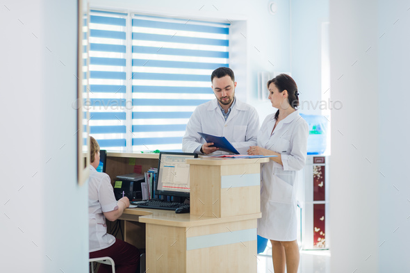 Busy reception in a hospital with doctors and receptionists - Stock Photo - Images