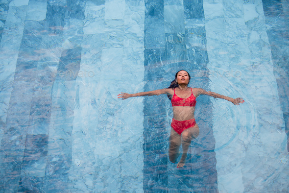 Enjoying vacation. Smiling beautiful young woman in swimming pool. - Stock Photo - Images
