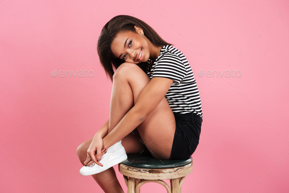 Smiling lovely african woman sitting and posing on a chair