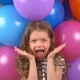 Little Girl on the Background of Multi-colored Balloons. Child Laughs and Rejoices