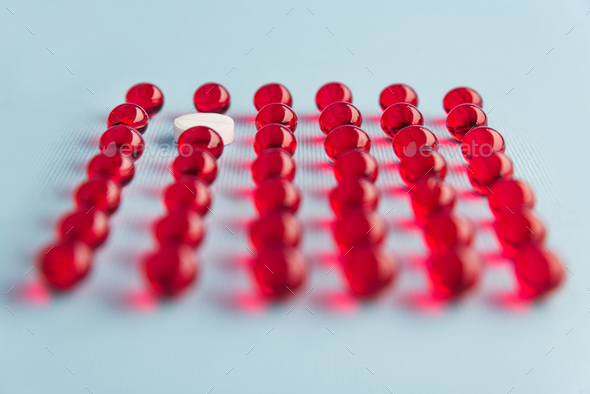 Close up of capsules with one white pill - Stock Photo - Images