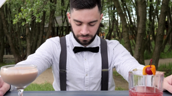 Bartender Behind Bar on Background Park, Barkeeper , Barmen Submit Alcohol, Colored Chilled Drinks