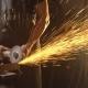 Sparks During Cutting of Metal Angle Grinder. Worker Using Industrial Grinder.
