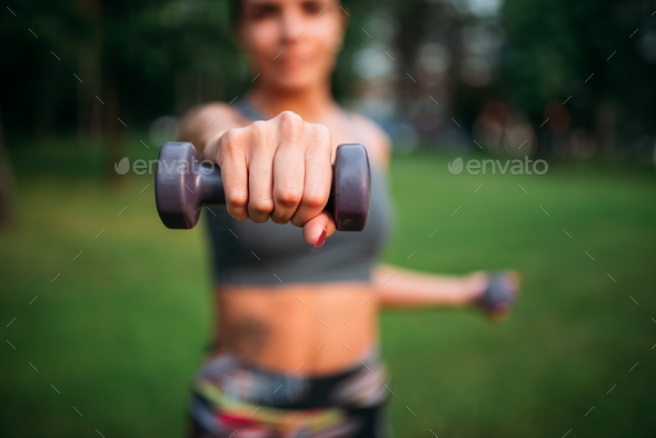 Sporty girl exercise with dumbbells in park - Stock Photo - Images