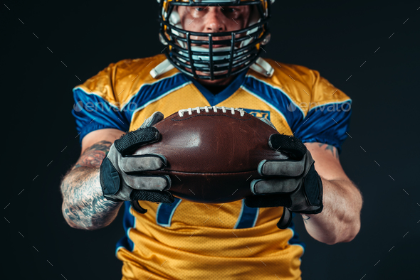 American football player with laced ball in hands - Stock Photo - Images