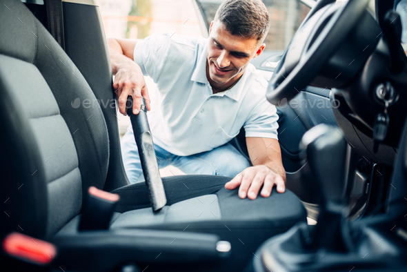 Man cleans car interior with vacuum cleaner - Stock Photo - Images