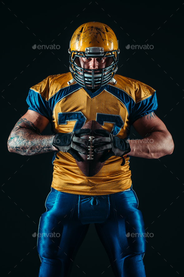 American football player holds ball in hands - Stock Photo - Images