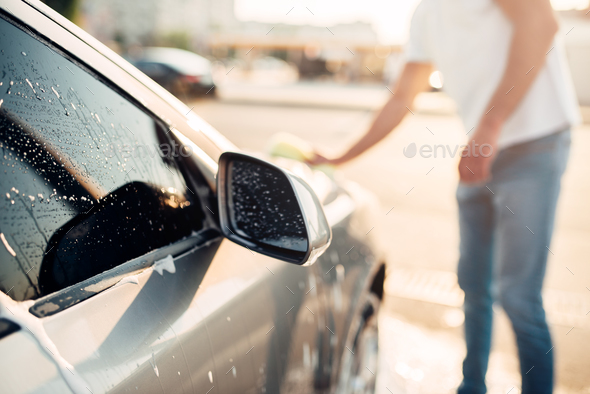 Male hand rubbing the car with foam, carwash - Stock Photo - Images