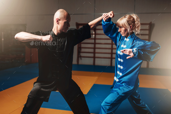 Male and female wushu fighters exercises indoor - Stock Photo - Images