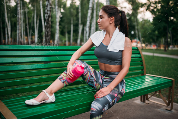Woman with sport bottle sitting on a bench in park - Stock Photo - Images