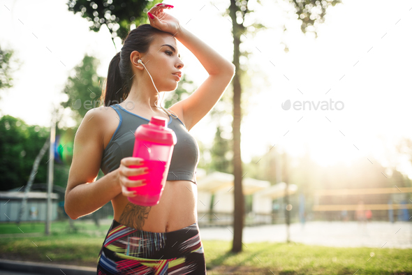 Woman with sport bottle, training in summer park - Stock Photo - Images