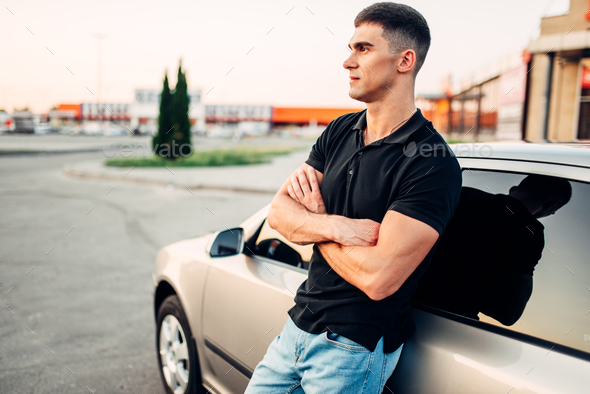 Smiling man standing near his car outdoors - Stock Photo - Images