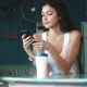 Sexy Girl Enjoys a Smartphone and Drinks Coffee Sitting in a Cozy Cafe