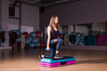 Sporty woman using step platform
