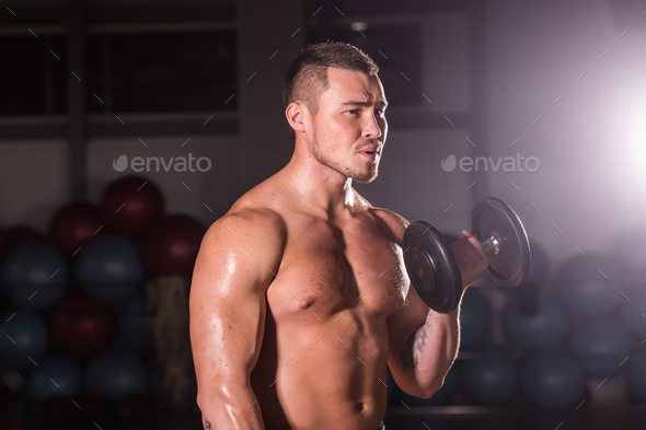 man working out in gym doing exercises with dumbbells at biceps - Stock Photo - Images