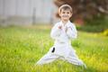 Preschool boy practicing karate outdoors