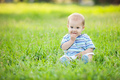 Happy small boy sitting on green grass in a park