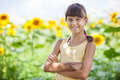 Smiling young girl against field of sunflowers