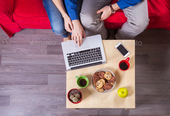 Young couple using laptop while sitting on couch