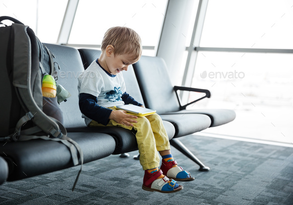 Little boy sitting in an airport departure hall and using his tablet