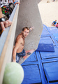 Male climber before jump on top handhold on artificial climbing wall