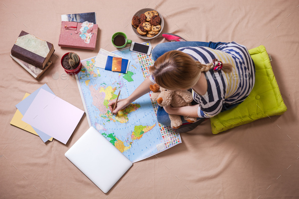 Young woman making marks on the map while sitting on the floor