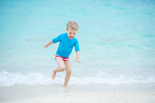 Happy little boy running in breaking waves on beach