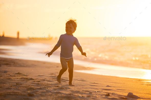 Happy little boy running on beach. Sunset light